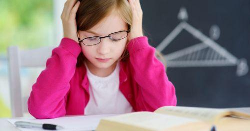 Ребенок в очках сидит над книгой