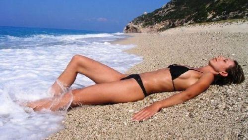 Девушка загорает на берегу моря