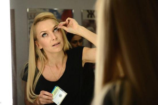 Женщина снимает контактные линзы