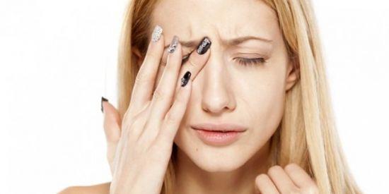 Женщина трет глаза руками